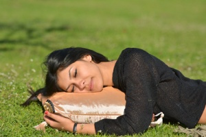 Young cute girl sleeping on pillow in fresh spring grass